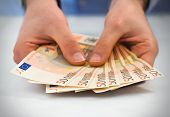 Man hands with stack of fifty euro banknotes.