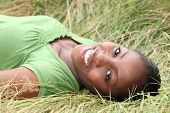 Beautiful smiling woman laying in the long grass