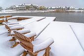 Snow Covered Lake Deck With Chairs In Winter poster