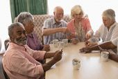 Front view of group of senior people playing cards around table in living room at home poster