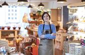 Portrait Of Smiling Female Owner Of Delicatessen Shop Wearing Apron poster