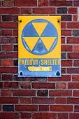 stock photo of nuke  - A weathered sign announcing a fallout shelter on an abandoned building on the Eastern seabord of the USA - JPG