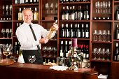 At the bar - waiter hold bottle white wine in restaurant