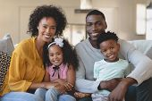Front view of happy African American family sitting on sofa and looking at in a comfortable home poster