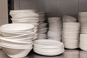A Pile Of White Clean Ceramic Porcelain Plates On A Metal Rack In The Back Of The Restaurant. Concep poster