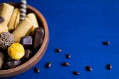 Preparation For A Banner With Sweets. Photo Of Chocolate Candies And Waffles On A Blue Background Wi poster
