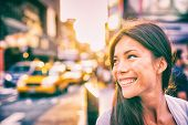 Happy people New York city lifestyle young Asian woman smiling in sunset walking in street with taxi poster
