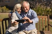 Front view of active senior Caucasian couple taking selfie with mobile phone in the park poster