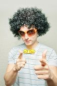 stock photo of dork  - funny guy in afro curly wig with eyeglasses and ribbon bow - JPG