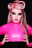 Young attractive freaky girl with fancy make-up and hairdo, in pink latex catsuit
