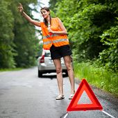 Young female driver wearing a high visibility vest, calling the roadside service/assistance after he
