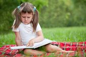 Little Cute Girl Preschooler With Book On Plaid In Park