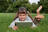 Girl Teenager Holding Tablet Wireless Computer Relaxing In Sunny Park