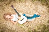 Happy Girl With Guitar Lying On Grass In Meadow.