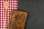 Cuchara de madera y coockbook en una placa de la pizarra