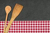 Wooden spoon on a slate plate with a red checkered tablecloth