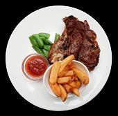 Steak with french fries and hot sauce isolated on black