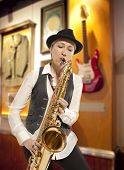 Saxophonist. Middle aged woman playing on saxophone against the background of rock cafe