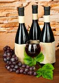 Composition of wine bottles, glass and  grape, on stone background