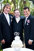 Handsome gay couple and their minister at their wedding.