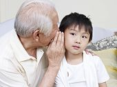 stock photo of grandpa  - asian grandpa whispering, telling grandson a secret.