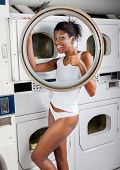 Portrait of young woman in undergarments gesturing thumbs up while standing by dryer in laundry