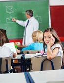 Bored little schoolgirl sitting at desk with teacher teaching geometry in classroom