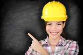Female construction worker or engineer showing pointing at empty blackboard with copy space for your