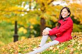 Fall woman relaxing happy in autumn forest foliage sitting down looking at copy space with colorful yellow, orange and red leaves in background. Mixed race Asian Chinese / Caucasian female girl model.