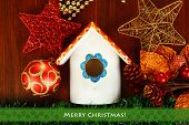 Nesting box and Christmas decorations on wooden background