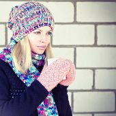 Young Woman With Coffee Cup Winter Time Wearing Knitted Sweater, Hat And Scarf With Mittens Lifestyl