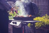image of charcoal  - Man is Cooking Meat On a Barbecue Outdoors