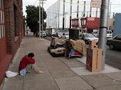 Homeless Man Sits On Sidewalk With Shopping Carts Full Of His Stuff On The Other Side Of Sidewalk
