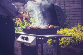 stock photo of braai  - Man is Cooking Meat On a Barbecue Outdoors