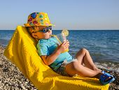 Boy Kid In Armchair With Juice Glass On Beach