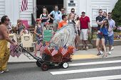 Man pushing giant oyster in the Wellfleet 4th of July Parade in Wellfleet, Massachusetts.
