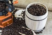 Scattered Roasted Coffee Beans By Coffee Grinder And Wooden Barrel