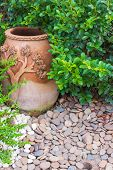 image of slut  - Pottery bowl decorated with river rocks in the garden - JPG