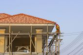 Man Worker On Scaffold Painting Roof