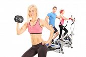 Three athletes exercising with fitness equipment isolated on white background