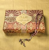 A tag with 'Eid Mubarak' message in arabic script on a golden gift box along with islamic rosary
