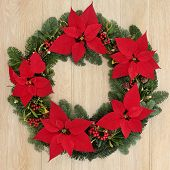 Poinsettia flower wreath with holly, fir, mistletoe and pine cones over light oak background.