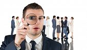 Composite image of businessman looking through magnifying glass against group of workers