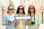 tourism, travel, vacation, direction and friendship concept - smiling teenage girls with white arrow