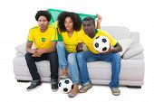 Brazilian football fans in yellow sitting on the sofa on white background