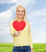 happiness, health and love concept - smiling woman with red heart