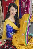 stock photo of dupatta  - Portrait of an Indian female dressmaker holding sari - JPG