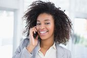 Casual businesswoman talking on phone smiling at camera in her office