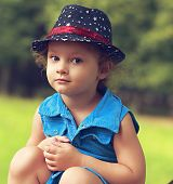 Fashion Beautiful Child Girl In Blue Jeans Dress Sitting And Looking Happy. Closeup Portrait
