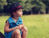 Fashion Kid Girl In Hat Sitting On Green Summer Background